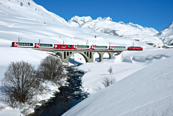 Switzerland. get natural. The Glacier Express crosses the creek Furkareuss in the snowed Urserental near the village Hospental in the canton of Uri. Schweiz. ganz natuerlich. Der Glacier Express ueberquert im zugeschneiten Urserental in der Naehe des Dorfes Hospental im Kanton Uri die Furkareuss. Suisse. tout naturellement. Le Glacier Express traverse la riviere Furkareuss, dans le neige Urserental pres du village Hospental dans le cantond d'Uri. Copyright by: Switzerland Tourism - By-Line: swiss-image.ch/Christof Sonderegger